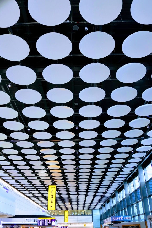a concourse at Heathrow airport with a spotted ceiling of white sound proofing discs