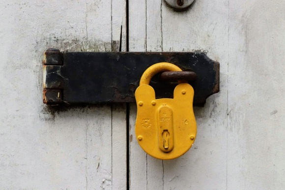 A bright yellow lock against a fades white shed door. I have adopted this as my avatar across my social media sites