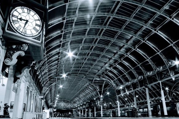 paddington sttaion at night. a view of the main GWR clock with a statue of Paddington Bear underneath