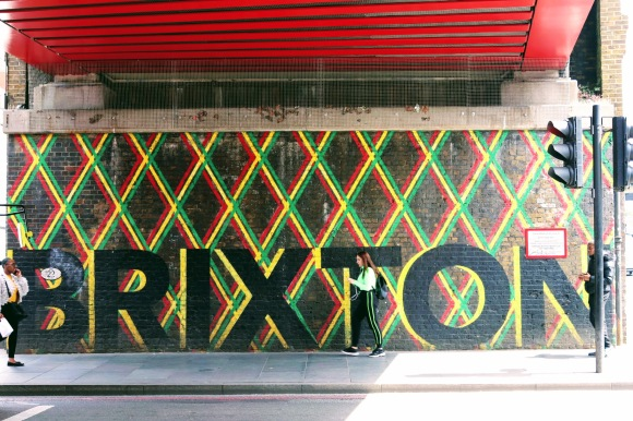 a painted 'BRIXTON' mural  with geometric green, yellow and red hatched stripes on a wall under the main bridge by the station