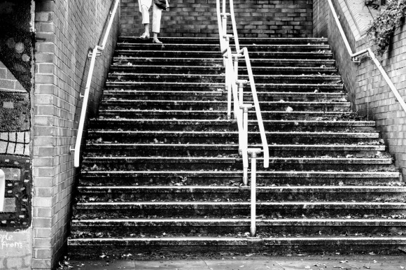 'A Step in Time' - a pedestrain walking down a flight of stairs leading to an underpass. The picture is in black and white