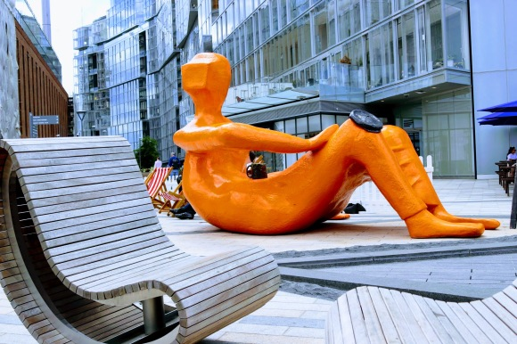 'Tea Break' - An orange figure reclining with a cup of tea outside Battersea Power Station