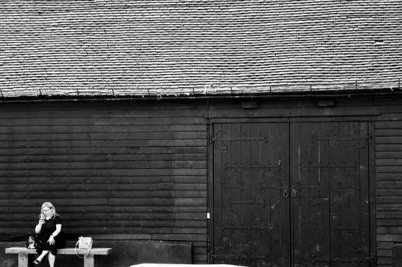 A black and white portrait of a woman sitting on a bench next to the Great Barn at Ruislip Farm buildings
