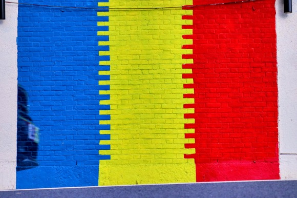 The Romanian flag colours painted on the side of a building - Blue, Yellow, Red