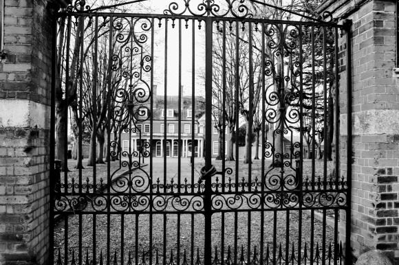 Upminster Court viewed through its ornate gates (closed), from the roadside