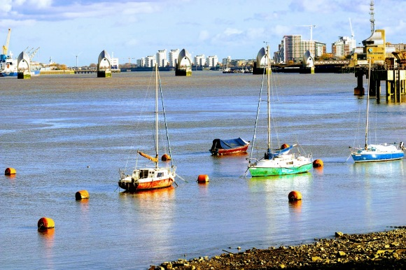 three yachts moored near the Thames south shore with the barrier in the near distance