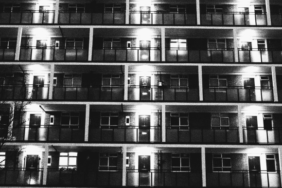 a five storey block of flats at night time and in black and white. The doors are lit up and the shot has an interesting symmetry