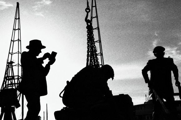 a black and white image os a statue of three dockers going about their business. The background also captures the shadowy image of some of the cranes used in the docking heyday