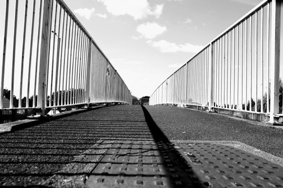 A view looking along the length of a footbridge with railings on either side focusing on a slightly cloudy sky