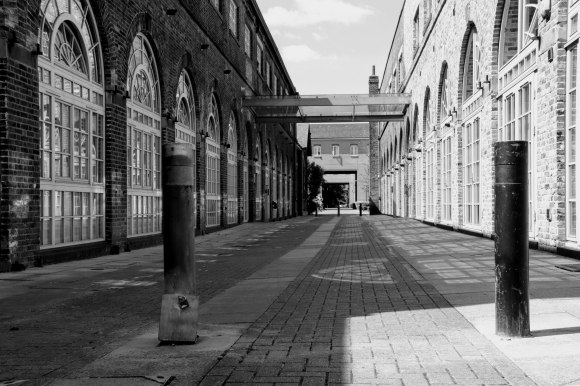 A view between two regenerated 'old railway works'. Taken in black and white with one side in the sun and the other in the shade