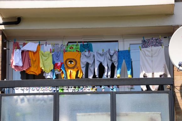 An array of colourful washing on a balcany of a high rise tower block
