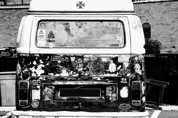 A rear view of a VW campervan covered in a variety of stickers. The image is in black and white