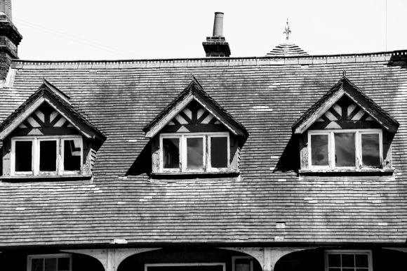 A black and white photo of a view of three dorma windows at roof level on the dilapidated pavillion style building