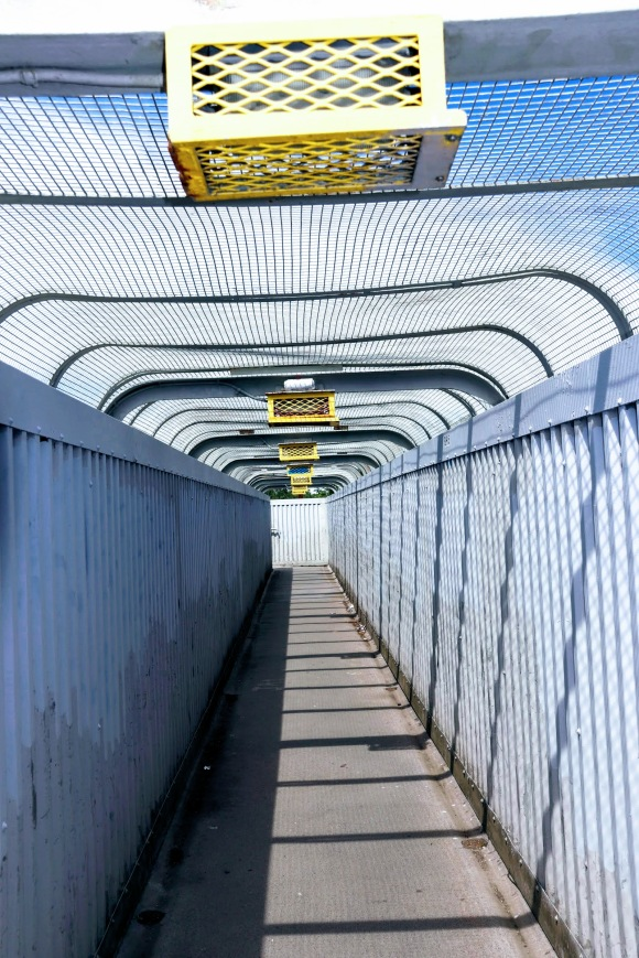 A colour photo looking along the length of a footbridge with tall sides and a mesh canopy. In the bright sunlight, the blue/grey metalwork contrasts with the yellow overhead light guards