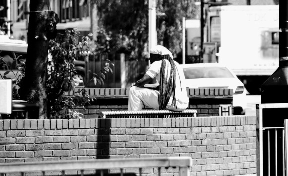 A black and white photo of a gent dressed in white shirt, trousres and headcap covering long dreadlocks who's sitting on a street bench
