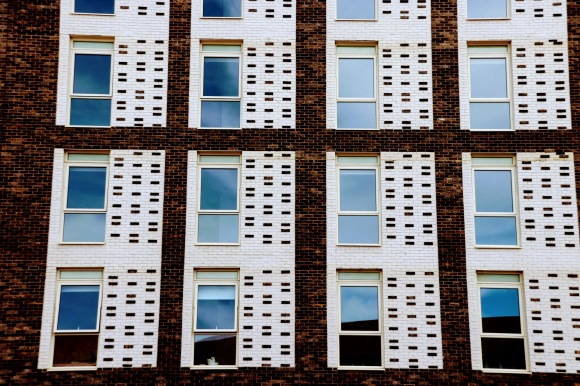 A colour photo of four columns of three vertical windows framed by white vertical bricks dotted with brown bricks to complement the main building brick colour