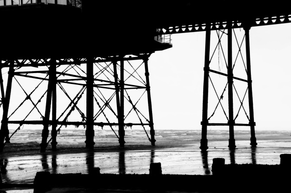 a black and white picture of eastbourne's pier supporting legs