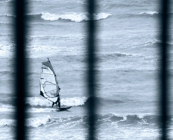 a black and white photo of a windsurfer caught beteen railings
