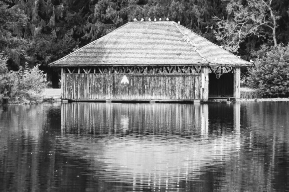 a black and white image of the boathouse in Tredegar Park with it's reflection on the lake's surface