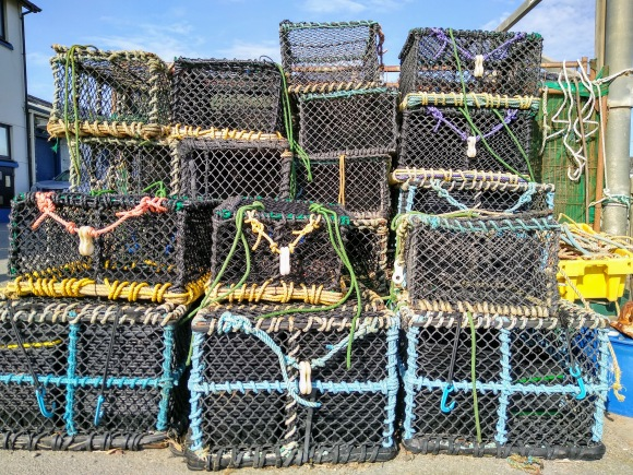 a collection of lobster pots stacked on top of each other at Aberystwyth Marina
