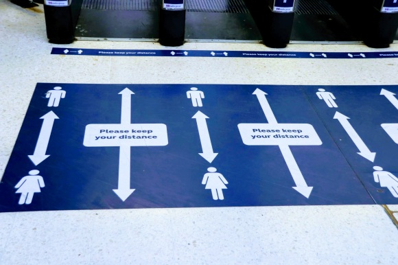 blue floor notices asking passengers to 'please keep your distance'