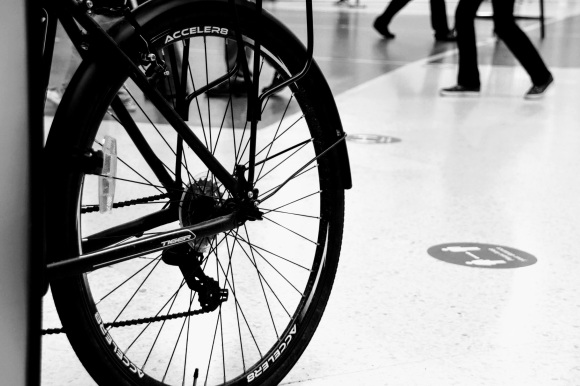 a blck and white shot of a bicycle tyre in the foregoround emblazoned with the makers name 'Acceler8'. Passengers feet walking by in the background