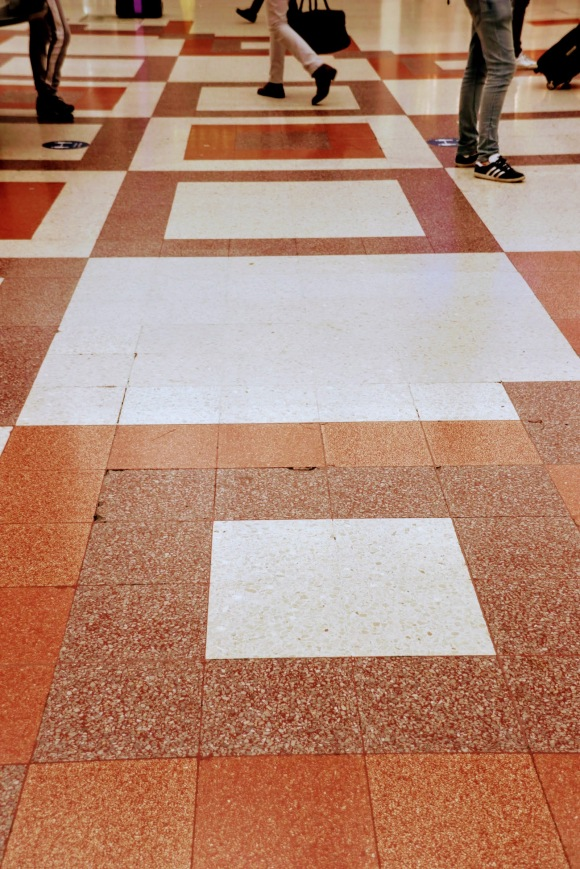 the mosaic floor in the station comprising of brown squares within brown squares in different shades and passengers walking over them
