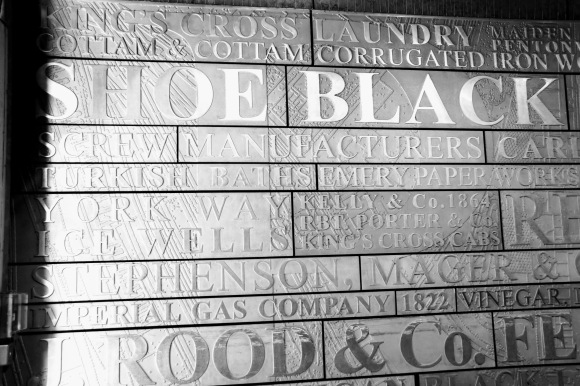 a wall plaque inside the 'Ironworks' complex promoting the complex's previous occupants e.g. laundry, shoe black, imperial gas company, screw manufacturers