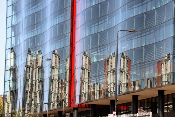 the wavy glass font of Kings pLace with dramatic reflections and a red stripe indicating where two panels meet