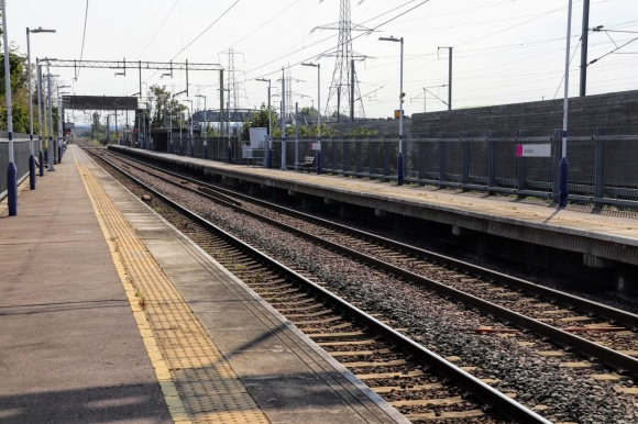 a lomg view along the length of an empty platform with the track extending as far as the eye can see. Overhead cables and nearby electricity pylons dominate the skyline