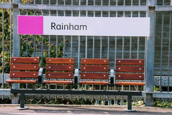 four empty eats on the plrtform under the station sign 'Rainham'