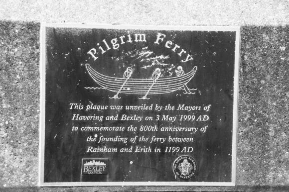 a plaque of three people in a boat rowing with the inscription: 'Pilgrim Ferry' - This plaque was unveiled by the Mayors of Havering and Bexley on 3rd May 1999 AD to commemorate the 800th anniversary of the founding of the ferry between Rainham and Erith in 1199 AD