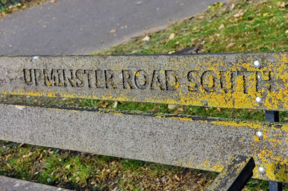 the back panel of a roadside bench with 'Upminster Road South'  engraved into it. The word 'south' is lichen encrusted