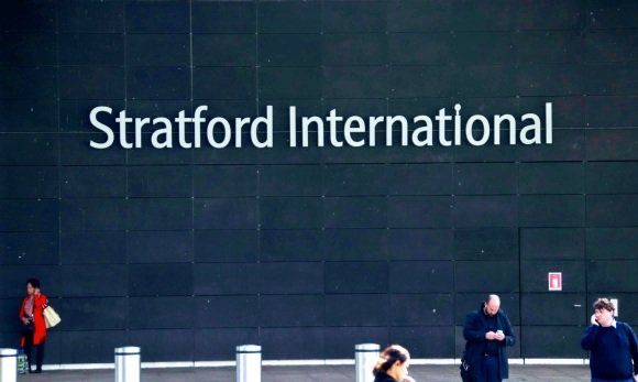 'Stratford International' sign on the side of the sttaion with four people in the foreground. One lady in a red coat stands out as she talks on her mobile.