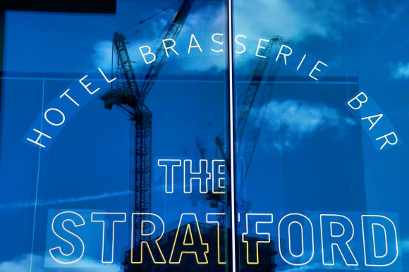 The entrance to 'The Straford', outline letters on the bottom of the picture and above in an arc 'Hotel Btasserie Bar'. The windown reflecting a blue sky and two cranes reflected
