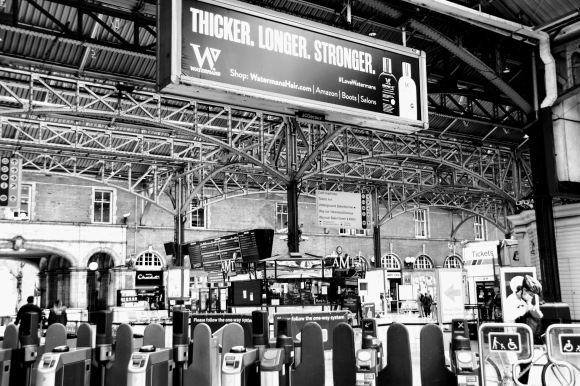 a black and white view over the platform gates into the main concourse devoid of many passengers.