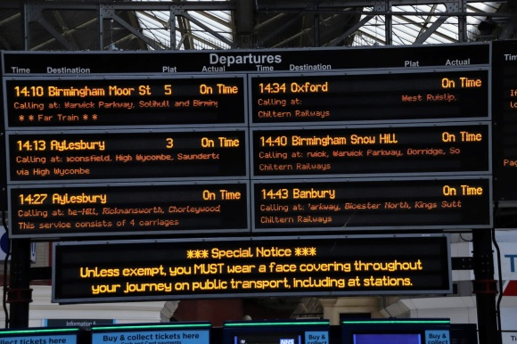 the main display board inside the station showing departures to 6 destinations. There's a Special Notice reminding everyone to wear a facemask