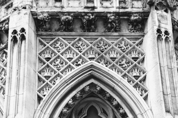 black and white image of a section of the Eleanor Cross outside the station. This section focusses on an array of rampant lions and three turretted castles over an arched window