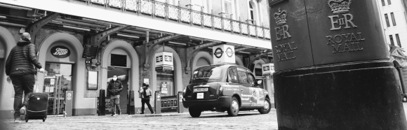 a black and white image of the station's forecourt with EIIR post box on right hand side, taxi  right centre and  a pedestrian making their way into the station pulling a wheelie suitcase