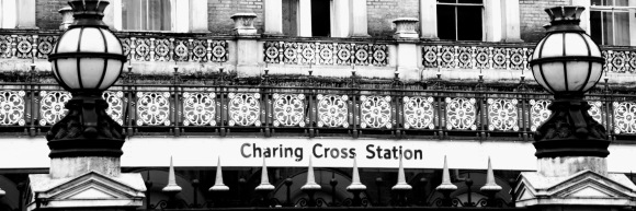 black and white 'letter box' image of the station name viewed through the front railings and flanked by decorative street lights