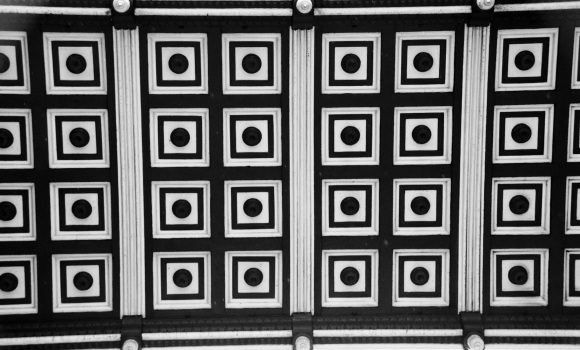 black and  white image under the footbridge. Showcasing the geometric design of a repeat of two rows of four squares within which there's a dot/circle. Each group of 2x4 shapes framed.