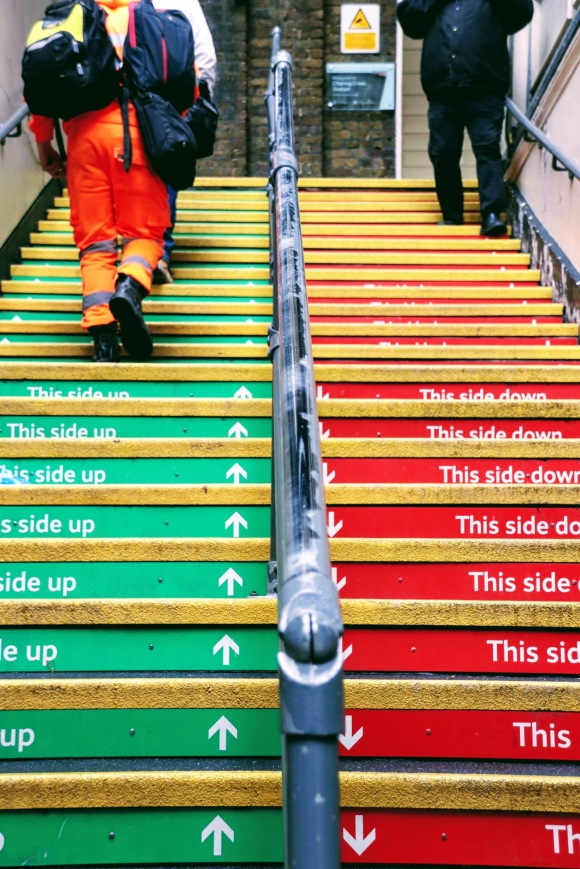 colour photo of narrow staircase leading into station. Left side has green flashing with arrows pointing up and text 'this side up'. Right hand side with down arrows on red flashing with text 'this side down'. pedestrians walking correctly as guided by the signs