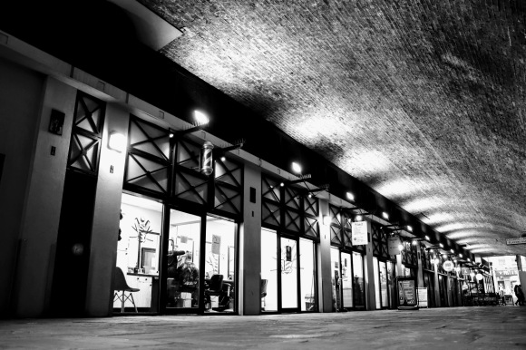 black and white 'moody' image of the Arches with uplighters highlighting  the curved roof. Shop windows all lit up