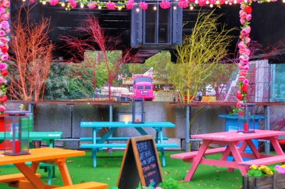 colour photo. The centrepiece in the distance is a pink 'Snog' double decker bus. The bus is frames through the colourful furniture display of the open air Beany Green eaterie. Picnic tables in green, orange, pink and cyan, framed by a string of pink flowers