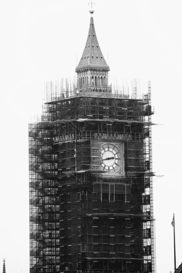 black and white of Big Ben tower encased in scaffolding. The only parts not covered are the clock face and the golden tower
