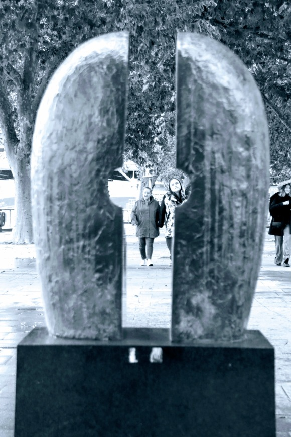 black and white with a blue hue. Two people looking through the sculpture. The best way to describe the sculpture is like a 'bum' (sorry), with a gap.