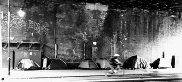 black and white image under Hungerford bridge of 6 camping tents of different sizes up against the bridge wall. A blurred passing cyclist gives a slight reference to speed