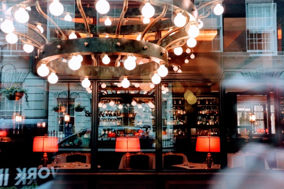 a colour image shot through the wondow of the restaurant. The image is a mixture of the main decorative ceieling and table lights inside, and a view of the buildings on John Adam Street reflected in the window