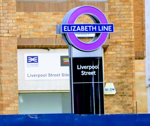 Colour: an Elizabeth Line purple roundel on top of a Liverpool Street sign