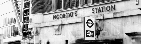 Black & White. 'Moorgate Station' sign above entrance along Moorgate with the Underground and Natiional Rail signs above the entrance